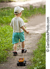 Little child boy playing car toy rope towing game