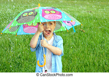 Child Trapped in Rain Storm with Umbrella - a young child is...