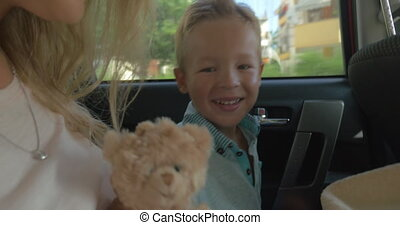 Child traveling by car with mother and toy