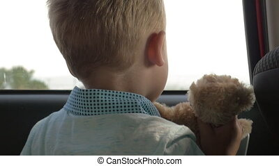 Child traveling in car with favourite teddy bear