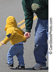 Child being looked after by a parent, keeping him from danger of vehicles passing by