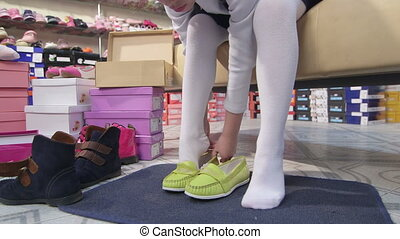 Child trying on new loafers for girls in children shoe store