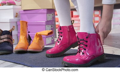 Child trying on new pink combat boots for girls in children shoe store closeup