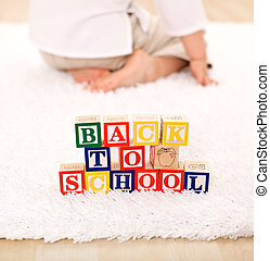 Child turning away from toy blocks - back to school theme