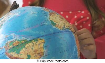 Child twists model of globe of world. Close-up