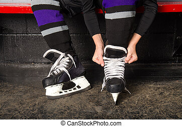 A child ties hockey skates in arena dressing room