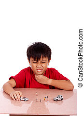 child under meditation of sore throat playing toy car