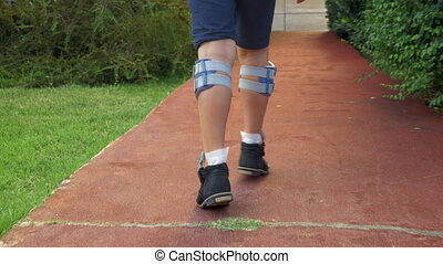 Slow motion steadicam shot of a kid walking outdoor with system of functional electrical stimulation. Treatment of foot drop with electrical signals stimulating the nerves in leg