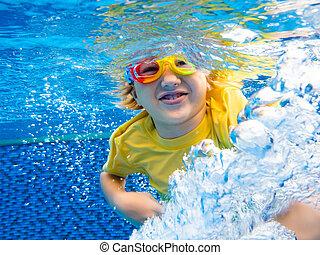 Child underwater in swimming pool. Kids swim.