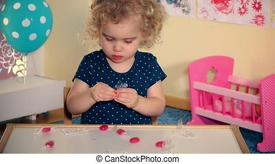 child unwrap sweets candies from paper and taste it wit...