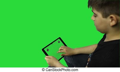 Child using a digital tablet  with green screen, back view