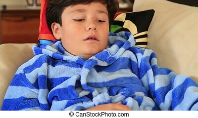 Young boy seated on a sofa taking asthma treatment with inhaler