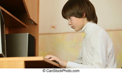 Child using desktop pc on wooden computer desk at home