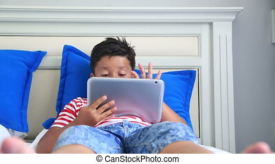 Child using digital tablet computer - Child lying on a bed...