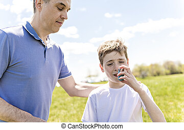child using inhaler for asthma outside in a park with his father
