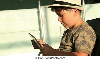 Child using ipad - Young boy gaming on tablet computer while...