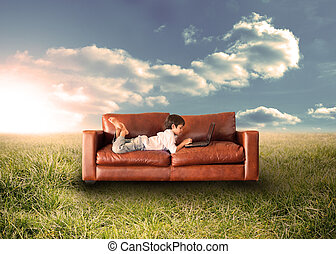 Child using laptop on couch in field