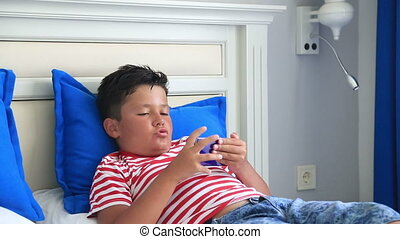 Child using smart phone - Child lying on a bed and using ...