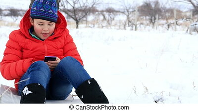 Child using smartphone in winter park