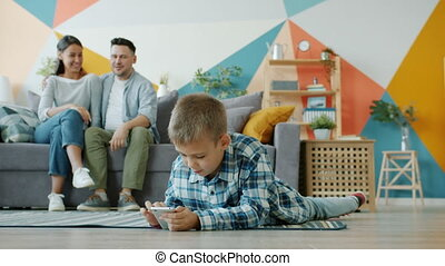 Child using smartphone touching screen while parents watching him talking at home
