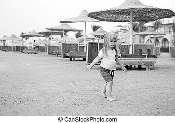 Child walk barefoot on sand on sunny day