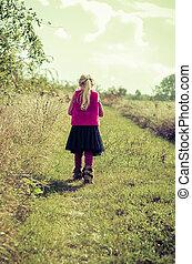 child walking away in rural path