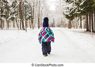 Child walking away in the forest on a winter day