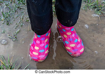 child walking in mud with multicolored boots
