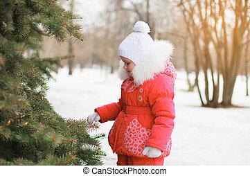 Child walking in snowy winter near christmas tree