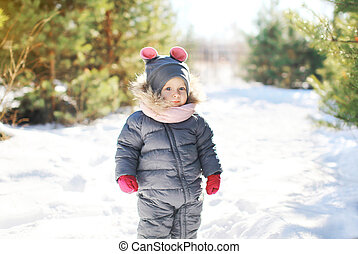 Child walking in sunny winter forest