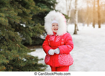 Child walking in winter forest near christmas tree