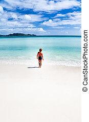 Child walking on a tropical beach