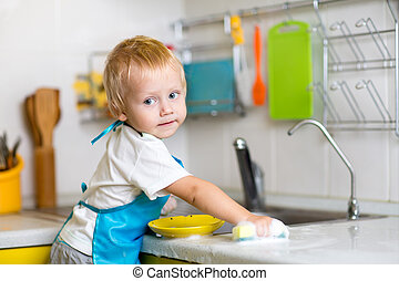 Child washing dishes in a domestic kitchen - Child boy...