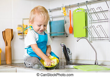 Child washing up in a domestic kitchen - Cute child boy 2...