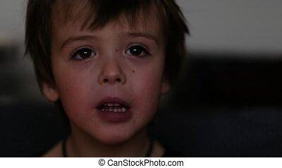 Child watching a cartoon in the dark