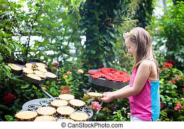 Child watching butterfly at tropical garden. Little girl...