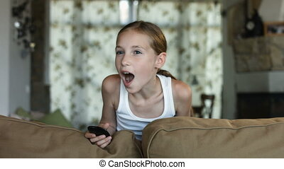 Child watching TV, little girl having fun on the couch, holding remote control