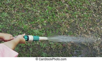 child watering dry grass