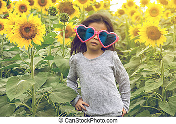 child wear Heart sunglasses with sunflower