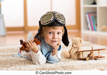 Child weared pilot or aviator plays with a toy airplane at home in nursery room. Concept of dreams and travels.