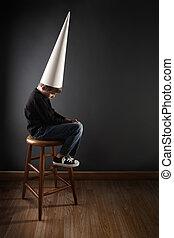 Child wearing a dunce cap