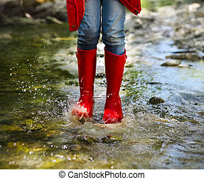 Child wearing red rain boots jumping. Close up