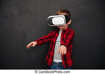 Child wearing virtual reality device over blackboard