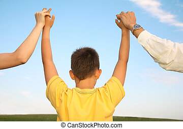 child, who holds for the hands of parents against the background of the sky