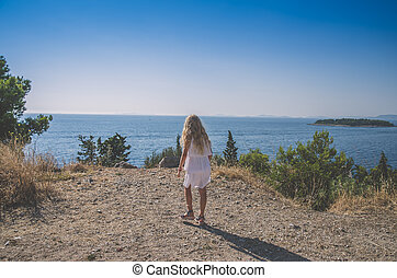child win white dress looking to the sea