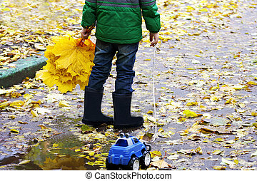 Child with a bouquet of leaves.