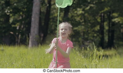 Child with a butterfly net running on a forest glade