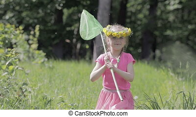 Child with a butterfly net running through a forest glade, on the head of a wreath of dandelions