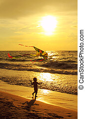 Child with a kite on the sea at sunset
