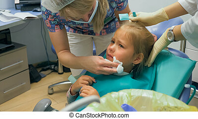 Child with a mother at a dentist's reception. The girl lies in the chair, behind her mother. The doctor works with an assistant. Procedure for drilling a tooth. Setting a temporary seal.